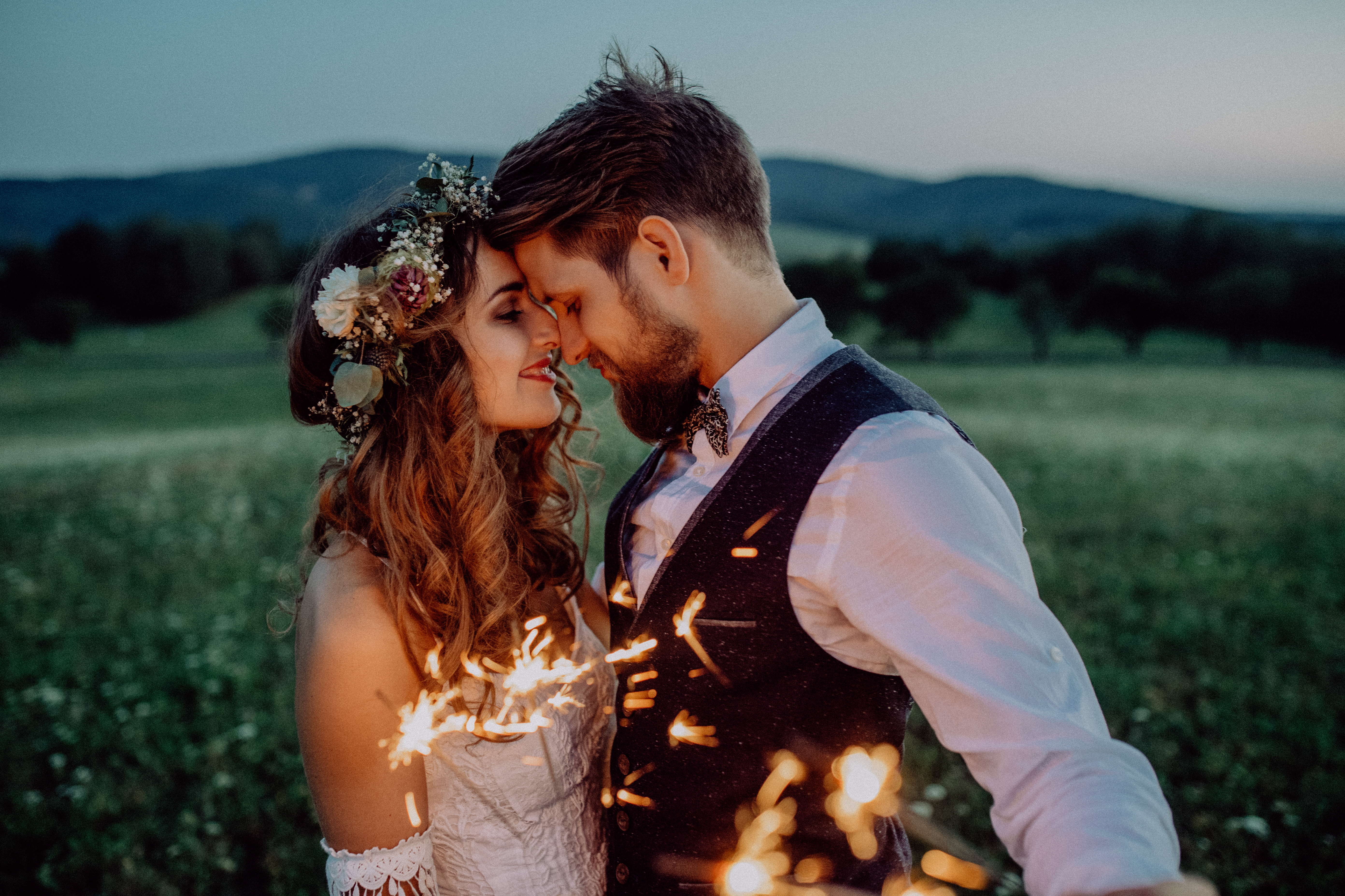 Beautiful bride and groom with sparklers on a meadow